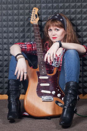 girl with electric guitar in studio