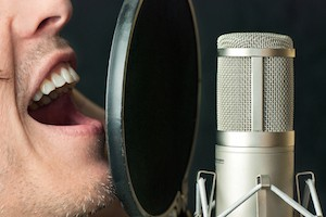 Super close-up of a man singing into a condenser microphone